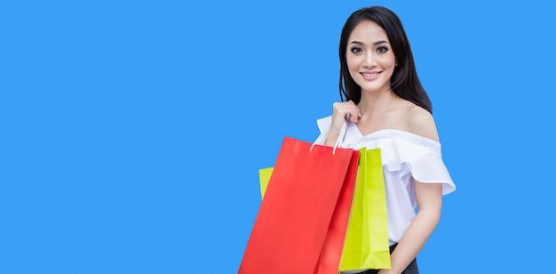 Mooie aziatische jonge vrouw met boodschappentassen met glimlach terwijl je bij de kledingwinkel. geluk, consumentisme, verkoop en mensen concept Premium Foto