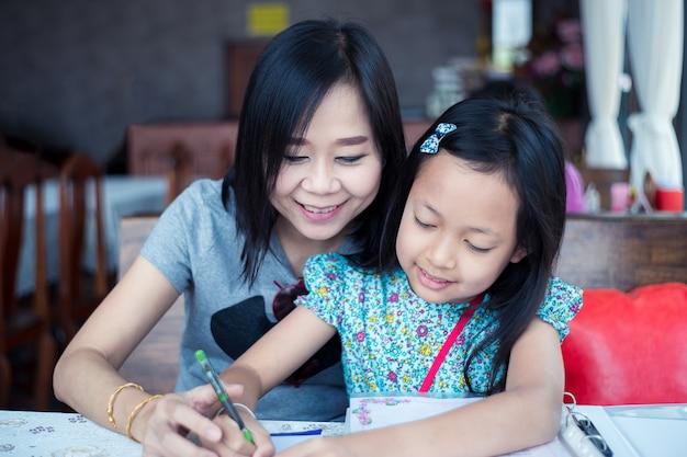 Mooie aziatische moeder die haar dochter met huiswerk helpt Premium Foto