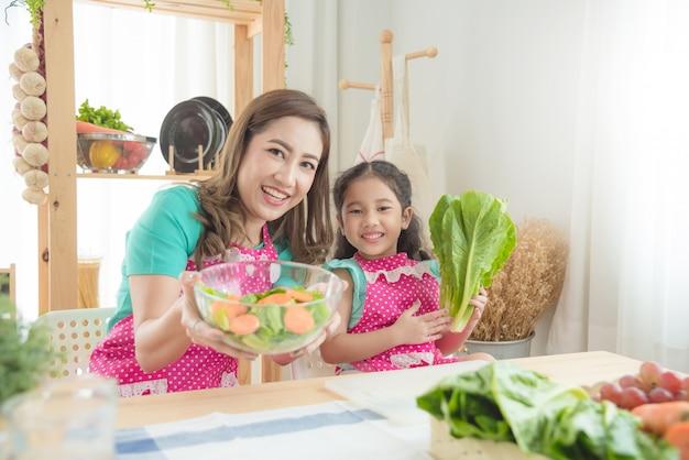 Mooie aziatische moeder en dochter die roze schort kokend ontbijt in de keuken dragen. Premium Foto