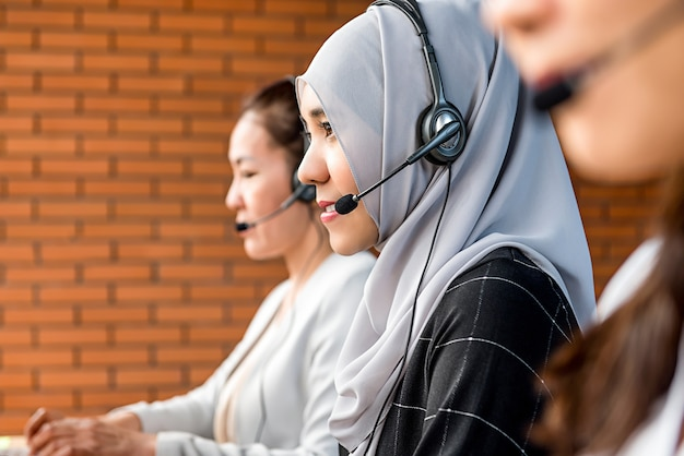 Mooie aziatische moslimvrouw die in call centre met haar team werkt Premium Foto