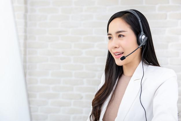 Mooie aziatische onderneemster die hoofdtelefoon draagt die in call centre werkt Premium Foto