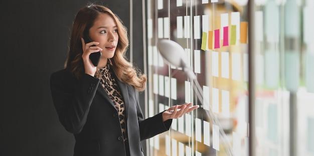 Mooie aziatische onderneemster die op de telefoon spreekt Premium Foto