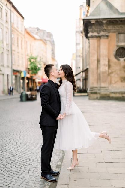 Mooie aziatische paar lopen en kussen in de stad. man is in zwarte luxe pak, vrouw in witte stijlvolle jurk Premium Foto