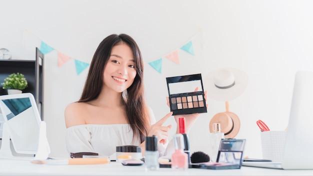 Mooie aziatische vrouw blogger laat zien hoe make-up en cosmetica te gebruiken. Premium Foto