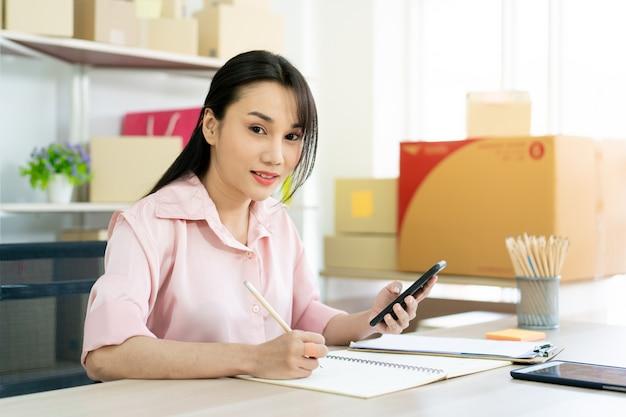 Mooie aziatische vrouw die berekeningen doet Premium Foto