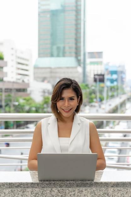 Mooie aziatische vrouw die in bedrijfsvrouwenkleren glimlachen die laptop computer en smartphone met behulp van Gratis Foto