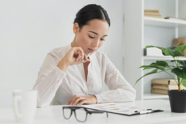 Mooie aziatische vrouw die in het bureau denkt Gratis Foto