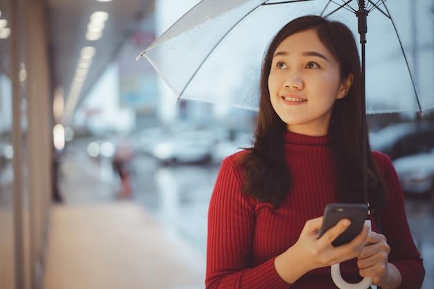 Mooie aziatische vrouw die lang door de straat loopt en een smartphone gebruikt terwijl het regent, vrouw die naar de winkel in het centrum kijkt. Premium Foto