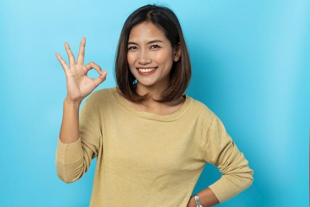 Mooie aziatische vrouw die met hand ok teken glimlacht Premium Foto