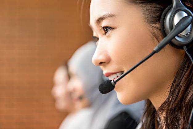 Mooie aziatische vrouw die microfoonhoofdtelefoon draagt die in call centre werkt Premium Foto