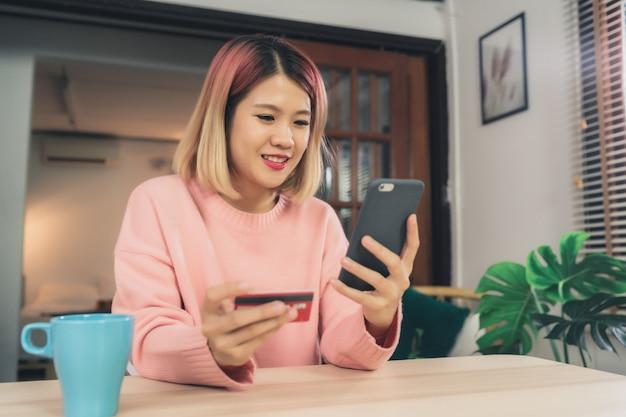 Mooie aziatische vrouw die smartphone gebruiken die online winkelend door creditcard kopen Gratis Foto
