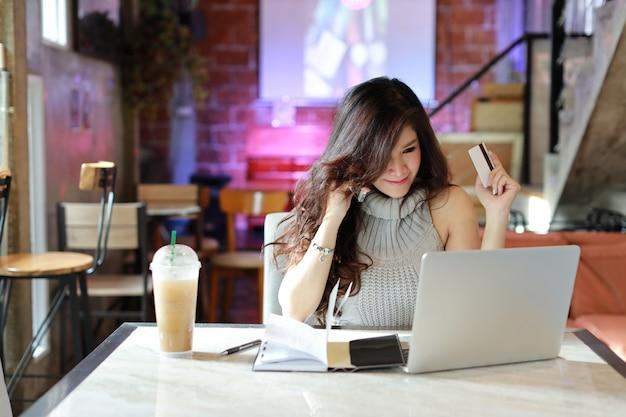 Mooie aziatische vrouw in casual kleding winkelen en online betaling op computer Premium Foto