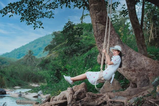 Mooie aziatische vrouw in een schommel aan de rivier Premium Foto
