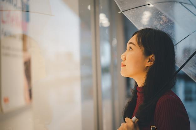 Mooie aziatische vrouw in rode sweater die zich naast de weg bevindt terwijl het regent en een paraplu houdt Premium Foto