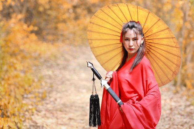 Mooie aziatische vrouw in rood chinees kostuum met oude paraplu en zwart oud zwaard met vreedzaam Premium Foto