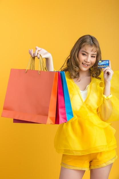 Mooie aziatische vrouw met in hand het winkelen zak en creditcard Gratis Foto