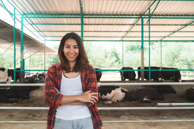 Mooie aziatische vrouw of boer met en koeien in de stal op melkveehouderij-landbouw Gratis Foto