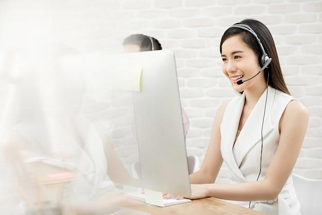 Mooie aziatische vrouw telemarketing klantenservice werken in callcenter Premium Foto