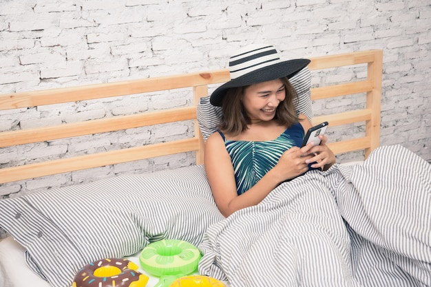 Mooie aziatische vrouw wat betreft tablet slimme telefoon en het eten van popcorn op bed Premium Foto