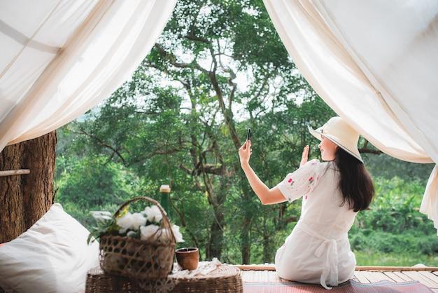 Mooie aziatische vrouwelijke toerist op haar kamer in het wild Premium Foto