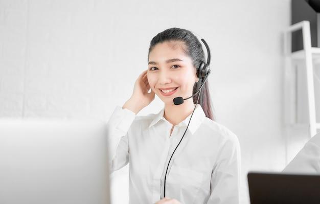 Mooie aziatische vrouwenadviseur die microfoonhoofdtelefoon van de exploitant van de klantenondersteuningstelefoon dragen op het werk. Premium Foto