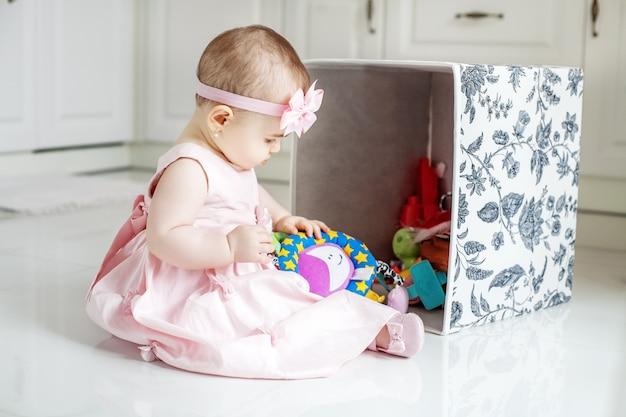 Mooie baby krijgt speelgoed uit de doos. roze jurk. Premium Foto