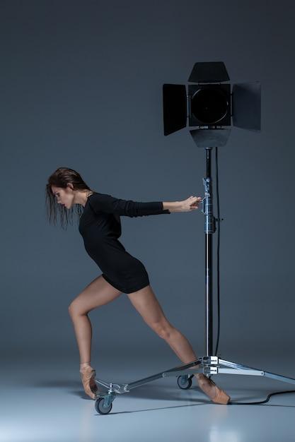 Mooie ballerina poseren op donkerblauw Gratis Foto