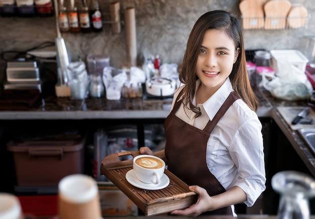 Mooie barista die bruine schort draagt die hete koffiekop houdt diende aan klant met smili Premium Foto