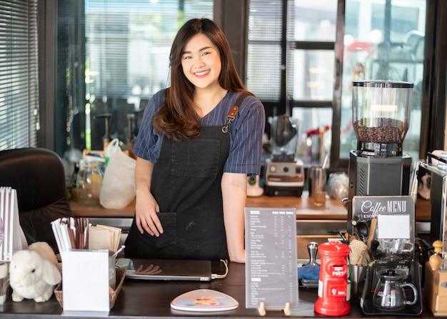 Mooie barista lacht in haar koffieshop Premium Foto