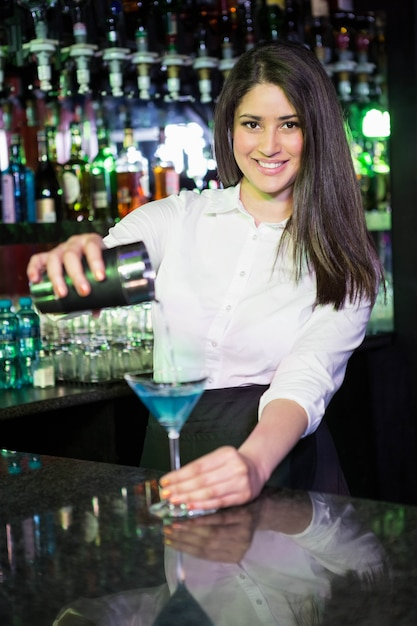 Mooie barman die een blauwe martini-drank in het glas gieten bij bar Premium Foto