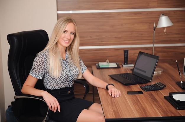 Mooie bedrijfsvrouw die met verkoop in haar bureau werkt Premium Foto