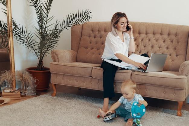 Mooie bedrijfsvrouw die thuis werkt. multi-tasking, freelance en moederschap concept Gratis Foto