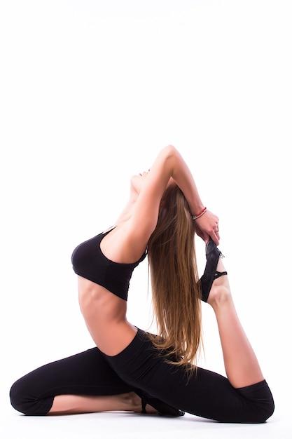 Mooie blanke lange vrouw balletdanser uitrekken warming-up volledige lengte geïsoleerde witte muur Gratis Foto