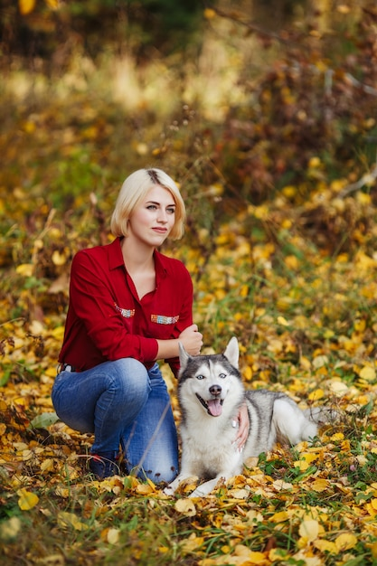 Mooie blanke meisje speelt met husky hond in herfst bos of park Premium Foto