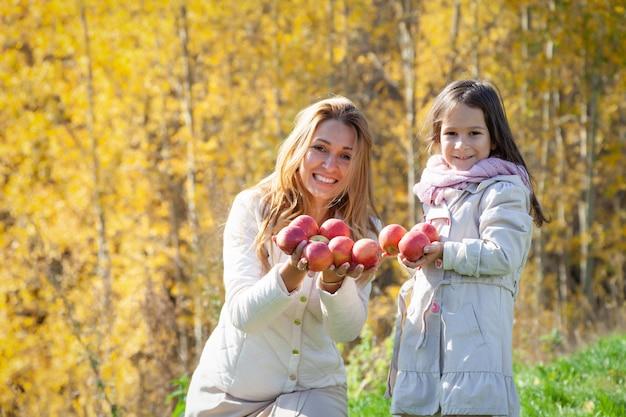 Mooie blanke moeder, dochtertje spelen met rijpe rode appels op achtergrond van groen gras van gouden bomen van herfst bos. concept familieweekend buitenshuis, mensen, weer, levensstijl Premium Foto
