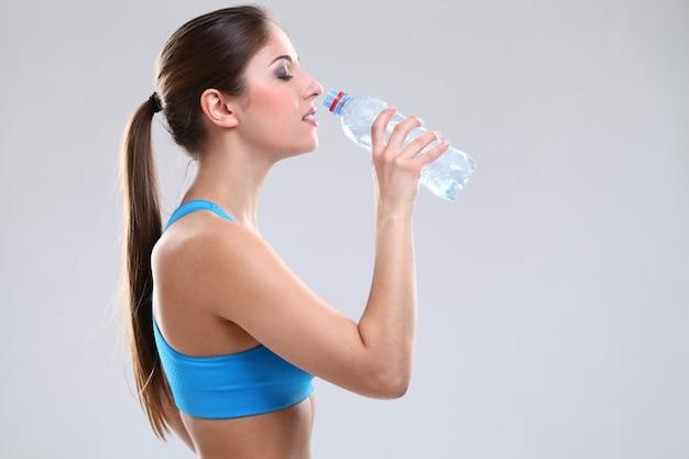 Mooie blanke vrouw in fitwear met water Gratis Foto
