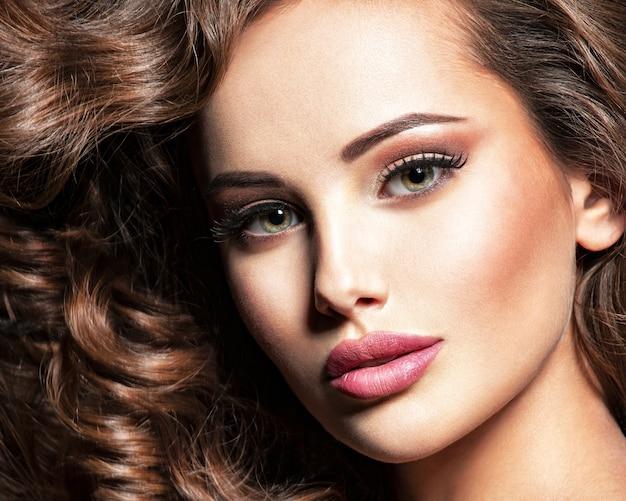 Mooie blanke vrouw met bruin krullend haar. portret van een vrij jong volwassen meisje. sexy gezicht van een aantrekkelijke dame die zich voordeed in studio over grijze achtergrond. Gratis Foto
