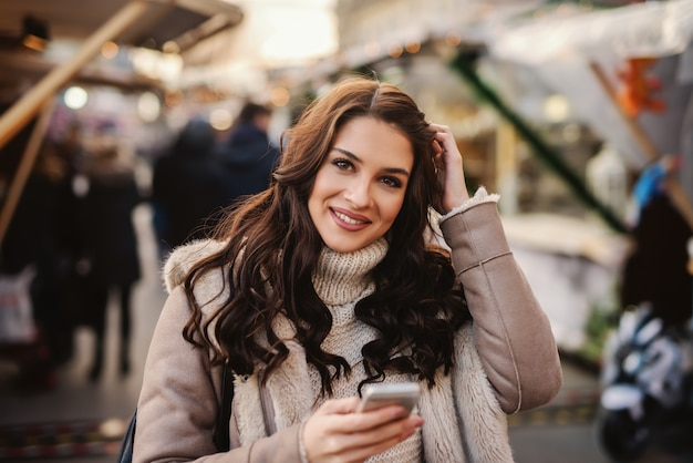 Mooie blanke vrouw met lang bruin haar staande op straat bij koud weer, met slimme telefoon Premium Foto