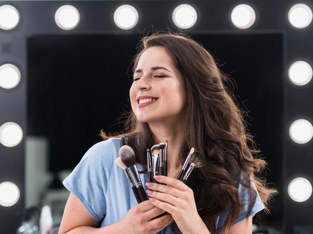 Mooie blije vrouw make-up stylist met borstels in handen Gratis Foto