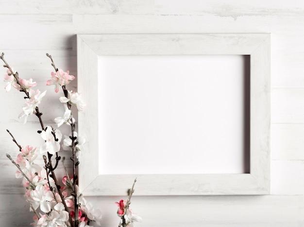 Mooie bloem en een frame op houten muur Gratis Foto