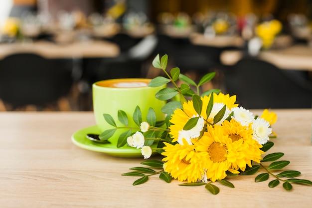 Mooie bloem en koffiekop op houten bureau met de achtergrond van de defocuskoffiewinkel Gratis Foto