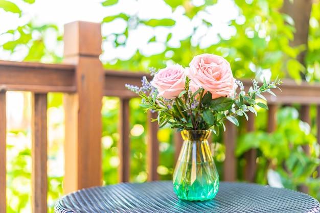 Mooie bloem in vaas op tafeldecoratie met uitzicht op de tuin Gratis Foto