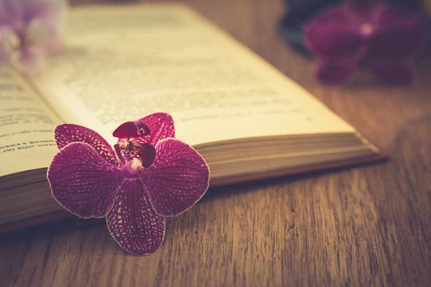 Mooie bloem met oud boek en kopje koffie of thee. romantische achtergrond met retro filtereffect Premium Foto