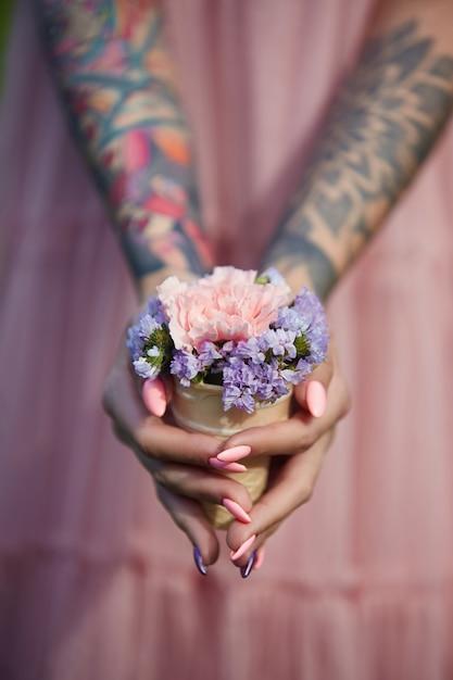 Mooie bloemen in het handenmeisje met tatoegeringen Premium Foto