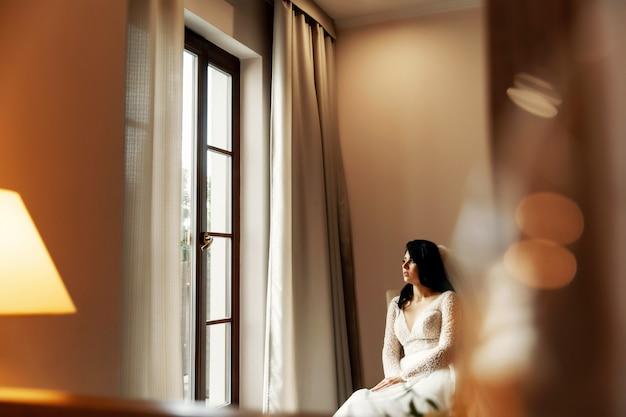 Mooie blonde bruid in luxe trouwjurk en mooie tweeling bruidsmeisjes in soortgelijke jurken in een ochtend in een loft ruimte met een spiegel en slinger van lampen. Premium Foto