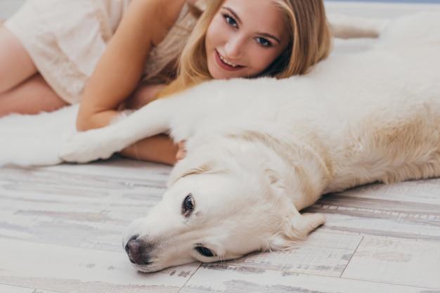 Mooie blonde die thuis op vloer met de hond ligt Premium Foto