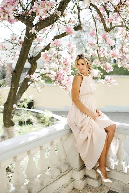 Mooie blonde in een lange jurk zit in de buurt van magnolia Gratis Foto