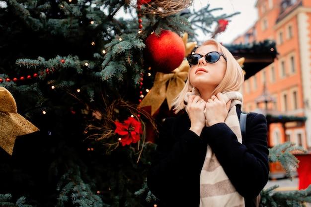 Mooie blonde in suglasses op de kerstmarkt in wroclaw, polen Premium Foto