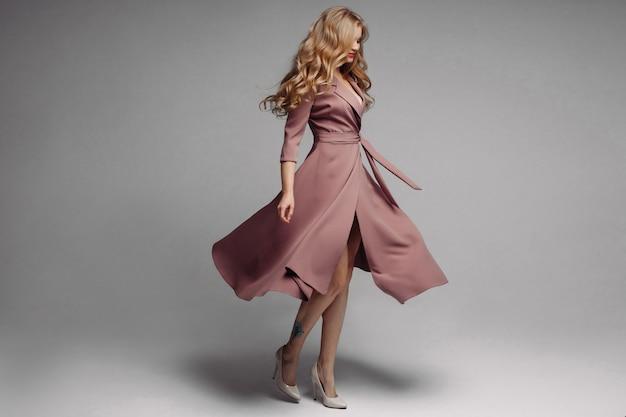 Mooie blonde langwerpige inktjurk en spinning Premium Foto