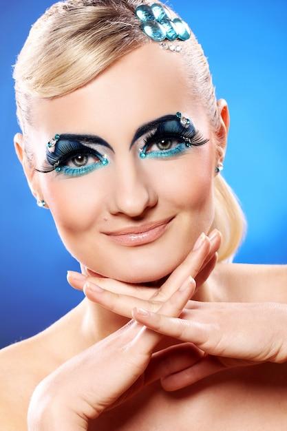 Mooie blonde met artistieke make-up Gratis Foto